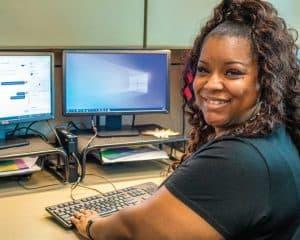 Quasha Dunham at her desk with computer screens