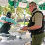 YEC staffer serving law enforcement officer hot dogs.