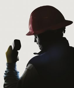 Silhouette of lineworker holding telephone