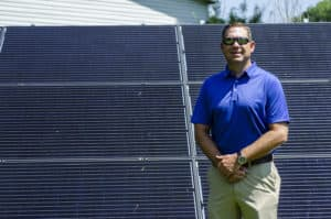 Brent Clinton stands next to solar panels