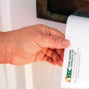 Hand putting YEC envelope through door mailbox slot