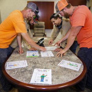 YEC Lineworkers looking at coloring contest submissions
