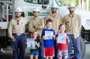 YEC kids display their coloring creations with lineworkers