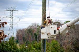 Lineworker in truck bucket working on utility pole
