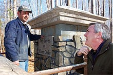 Todd Fields of Fields Masonry, far left, talks with May Green Properties developer Tom Smith as he builds an entrance column for The Coves on River Oaks. The stones, Smith notes, had been in storage for several years.