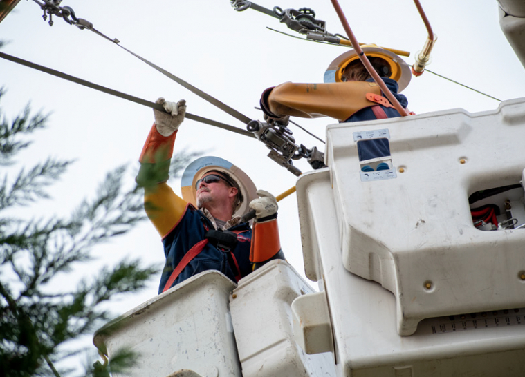 Photo D: YEC lineworkers tending to power lines