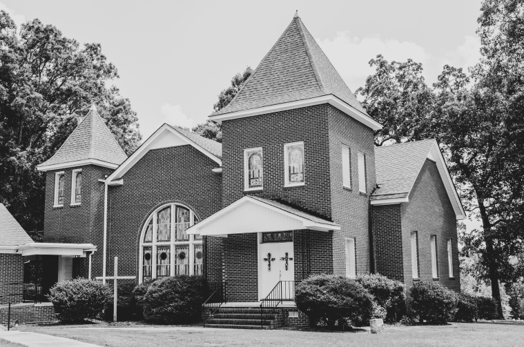 A red brick church with stained glass windows is pictured in black and white.