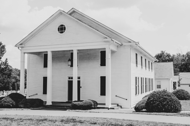 A white clapboard country church is pictured in black and white.