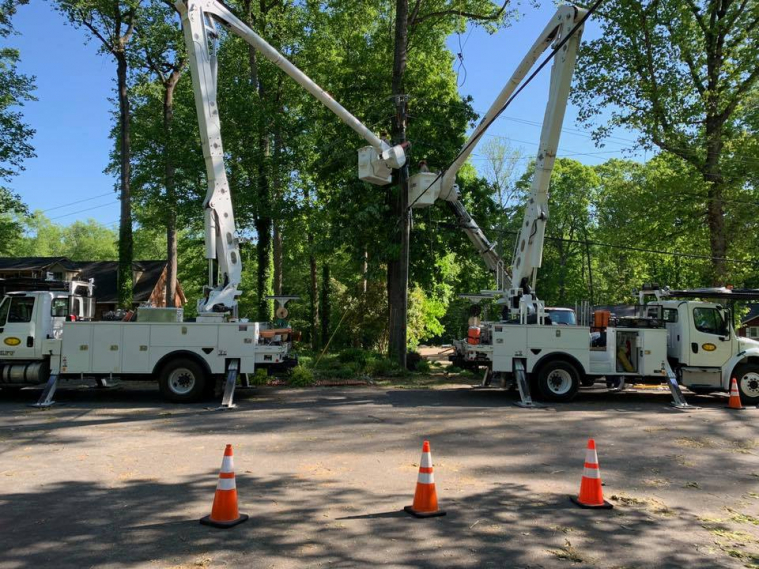 Two basket crane trucks backed up to a utility pole