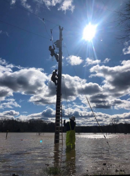 YEC lineworkers climbing a partially submerged utility pole with a crew member in hip waders standing below.